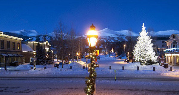 Holiday lights on trees, buildings and light posts in downtown Breckenridge with the mountains in the background.