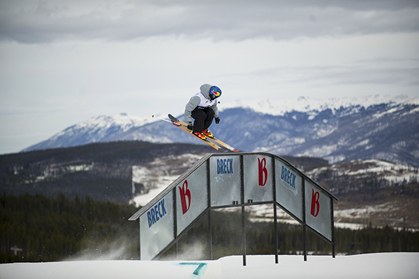 A skier catching air in the foreground with the mountains in the background.