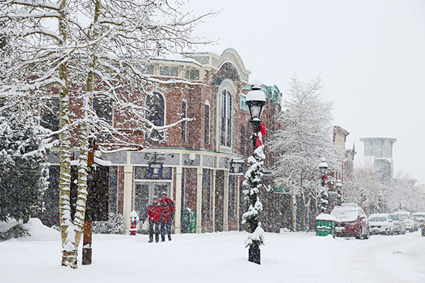 A couple takes a stroll on a very snowy day in front of the Victorian storefronts of Main Street, Breckenridge.
