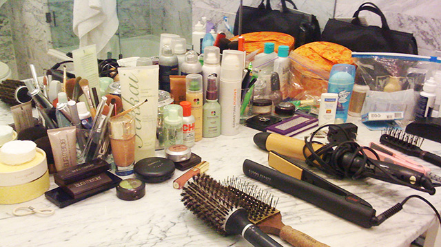 Multiple toiletry items, beauty supply items and makeup fill a bathroom counter.
