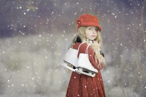 A young girl carrying ice skates with snow flakes falling around her.