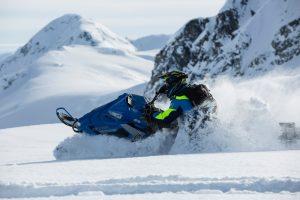 A person riding a snowmobile near two mountain peaks.