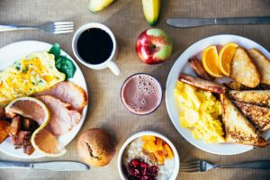 Breakfast plates with eggs, french toast and fruit plus a cup of coffee and a glass of juice.
