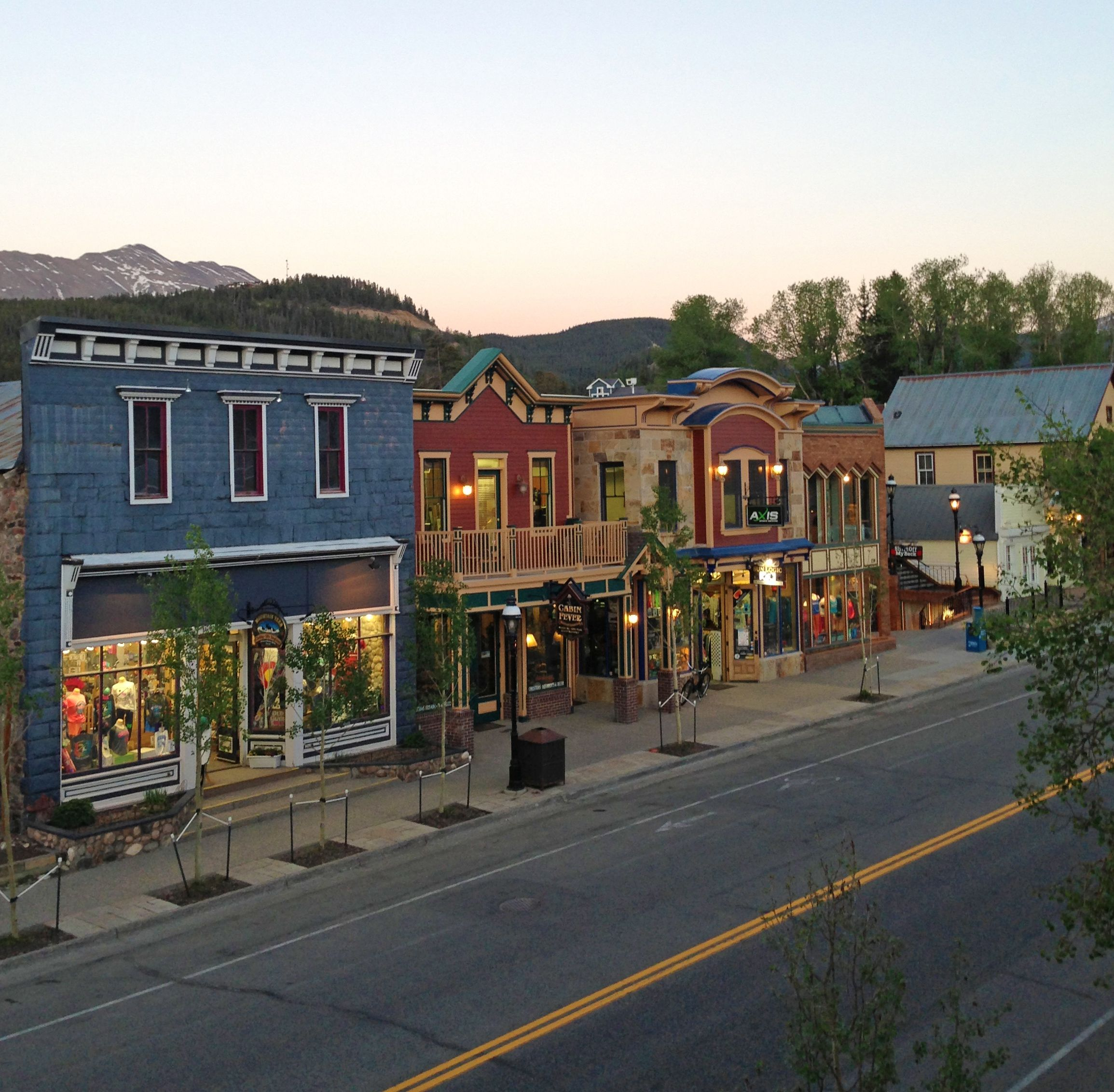 Storefronts on the east side of Main Street with Baldy Mountain visible behind.